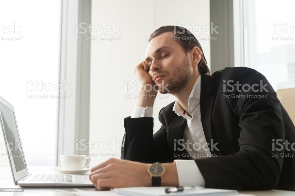 Young businessman dozed in front of laptop at work. stock photo