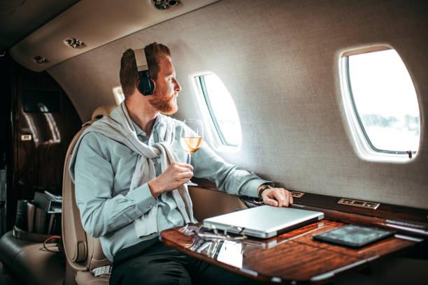 Junger Geschäftsmann Weintrinken auf einem privat-jet – Foto