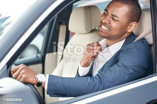Young mulatto businessman driver sitting inside the car driving holding collar aside feeling hot uncomfortable side view in opened window close-up