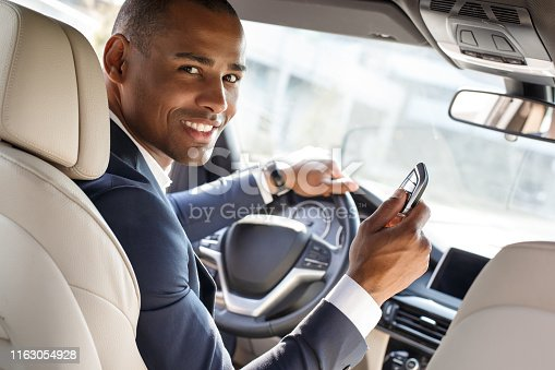 istock Young businessman driver sitting inside car with alarm controller looking camera happy back seat view 1163054928