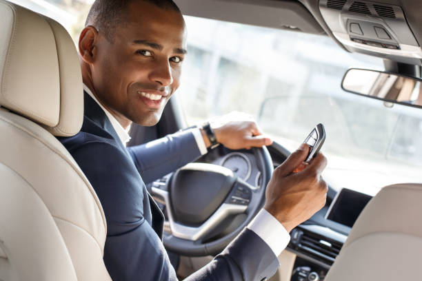 Young businessman driver sitting inside car with alarm controller looking camera happy back seat view stock photo