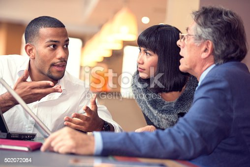 A young man of african descent trying to present his ideas to his colleagues. Shot in a relaxed cafe environment.