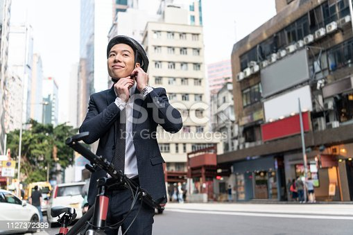 Cheerful Chinese man in his 20s wearing suit, preparing to cycle into work, safety, preparation