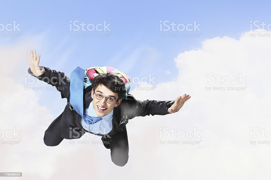 Young businessman flying with parachute on back royalty-free stock photo