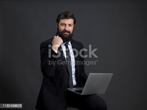 888751614 istock photo Young businessman gesturing victory 1132439523