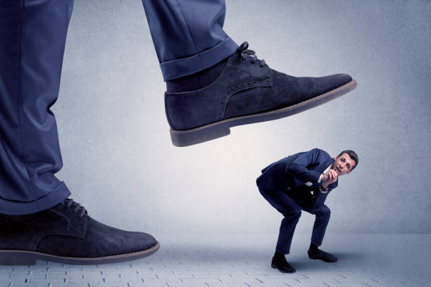 Young businessman getting crushed Young handsome businessman getting crushed by a big formal shoe cruel stock pictures, royalty-free photos & images