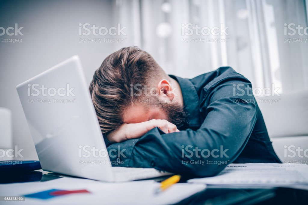 Young businessman getting tired and depressed working hard in the office stock photo