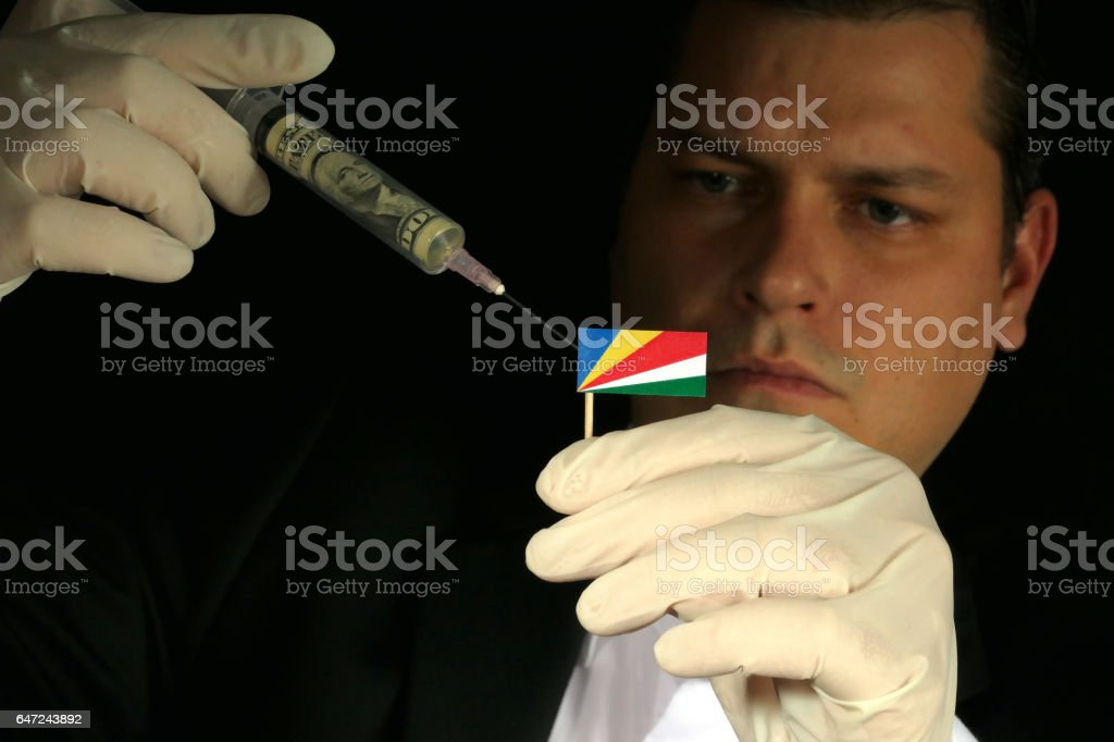 Young businessman gives a financial injection to Seychelles flag isolated on black background stock photo