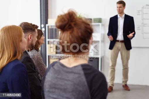 602323380 istock photo Young businessman giving presentation to a team 1146840490