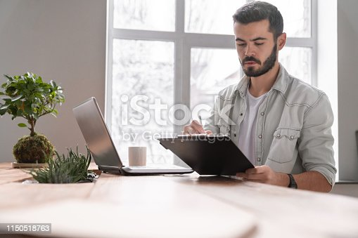 872006502 istock photo Young businessman going through paperwork at office 1150518763