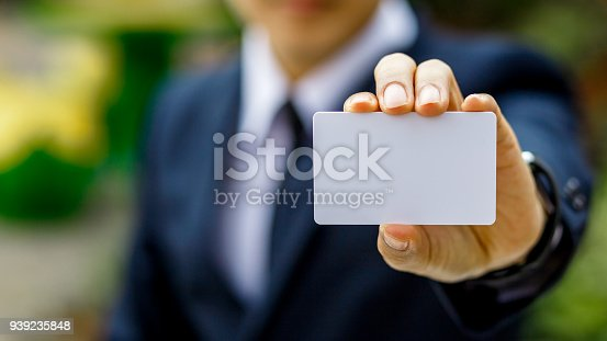 Young businessman hand holding blank white credit card mock up front side view, Empty plastic bank-card design mock up, white business name card mock up, money and finances concept
