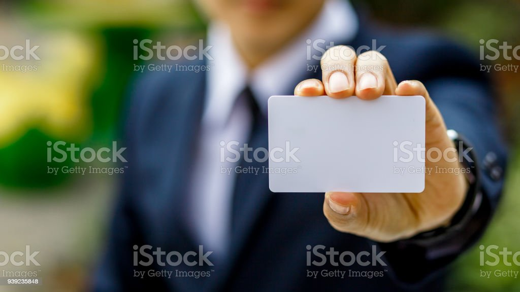 Young businessman hand holding blank white credit card mock up front side view, Empty plastic bank-card design mock up, white business name card mock up, money and finances concept stock photo