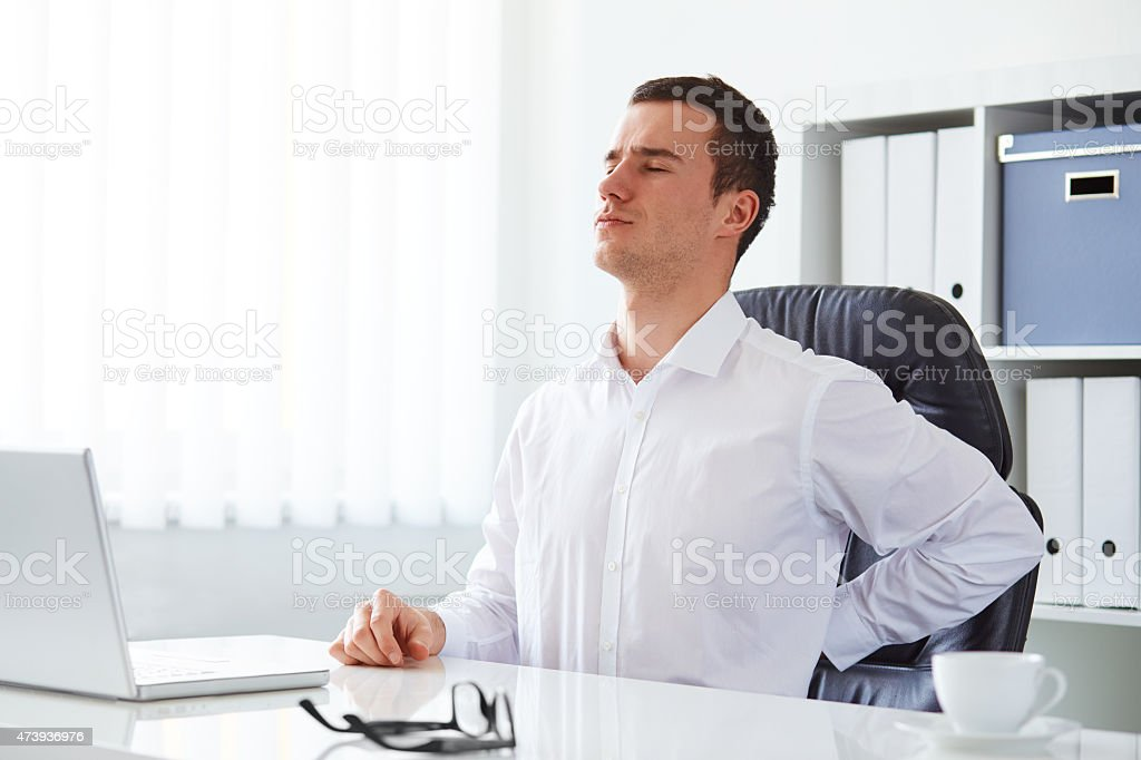 Young businessman has backache stock photo