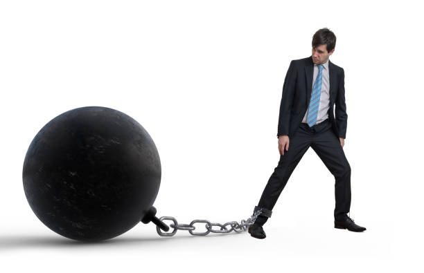 Young businessman has chained big metal ball to his leg. Isolated on white background. stock photo