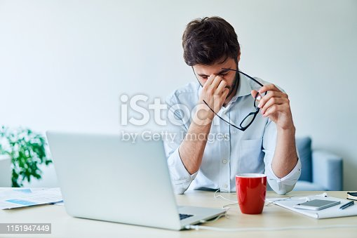 833210686 istock photo Young businessman having headache while working in home office 1151947449
