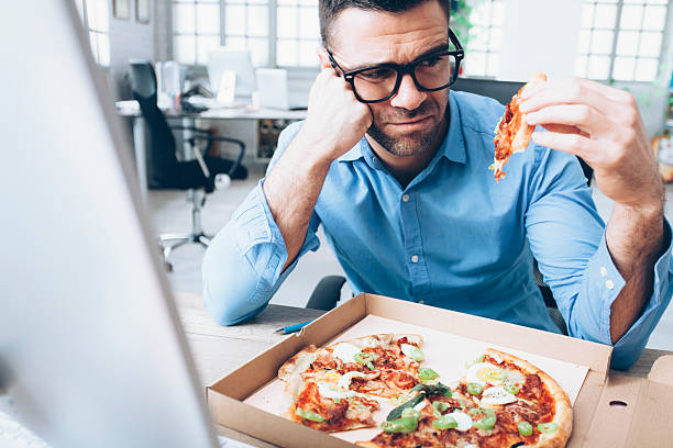 Young businessman having unpleasent pizza lunch break at workplace stock photo