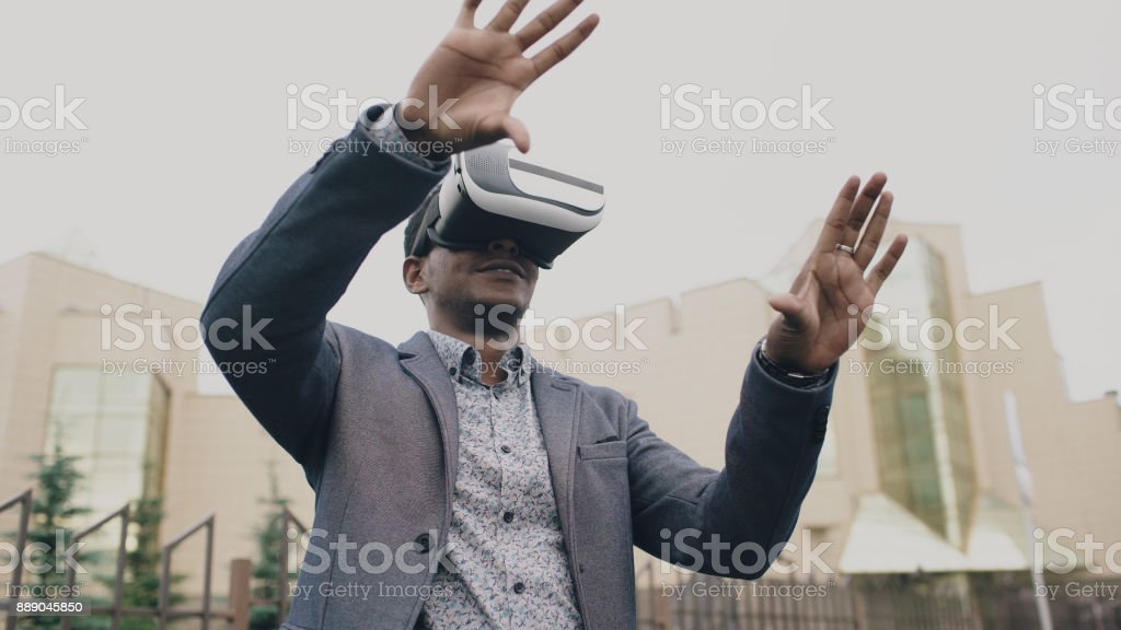 4f656db7675e Young businessman having VR experience using 360 virtual reality headset  outdoors - Stock image .