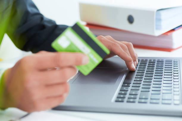 Junger Geschäftsmann hält eine Kreditkarte und eingeben. Online-Einkaufen im Internet mit einem Laptop. Nur die Hände über den Tisch – Foto