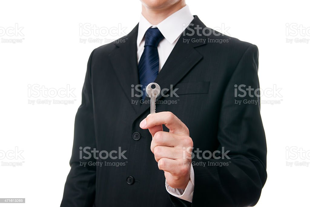 Young businessman holding a key in hand stock photo