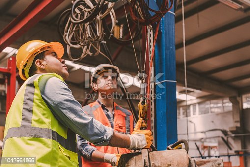 Skilled handsome Industry workers and manager man with crash helmet and worker west using overhead crane controller and pushing button while managing crane at industrial tractor plant shop