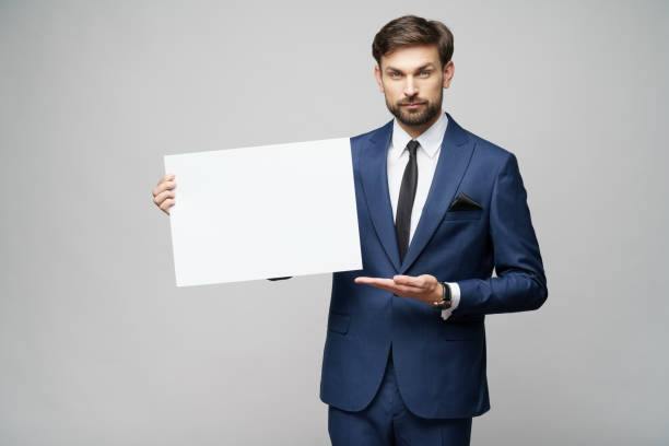 Young businessman holding blank signs over grey background stock photo