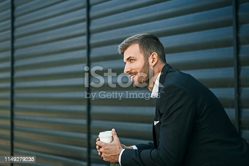 Young businessman holding coffee to take away at early morning