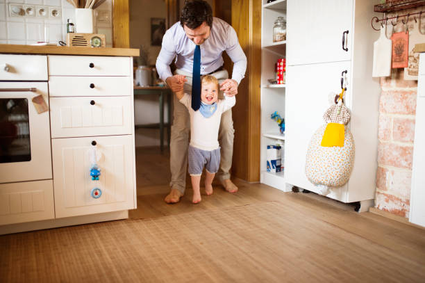 Young businessman holding hands of his son taking first steps. stock photo