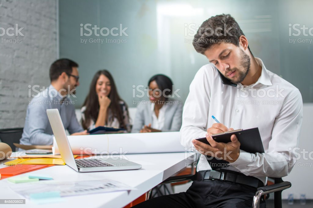 Young businessman holding mobile phone between ear and shoulder talking and writing notes to clipboard in modern office, while his business partners having meeting in the background. stock photo