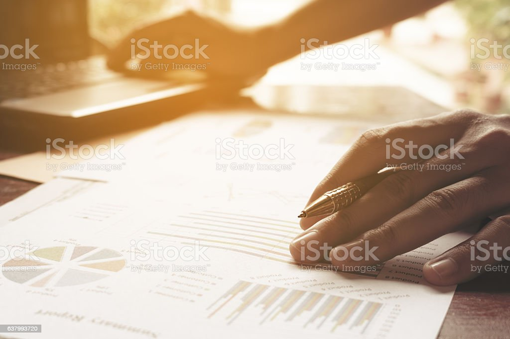 Young businessman holding pen on charts and graph stock photo
