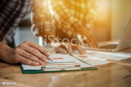881542122istockphoto Young businessman holding pen pointing graph chart and partner u 881541416