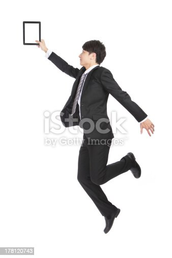 istock Young Businessman Holding Tablet PC Jumping 178120743