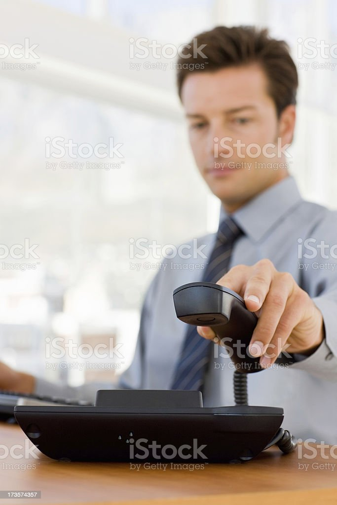Young businessman holding telephone receiver royalty-free stock photo