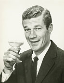 Young businessman holding wine glass, (B&W), portrait