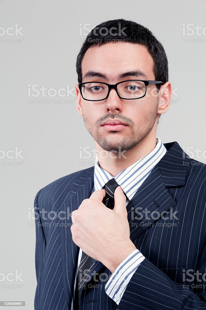 Young businessman holds tie stock photo