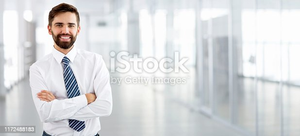 Young businessman smiling looking at camera in a modern office