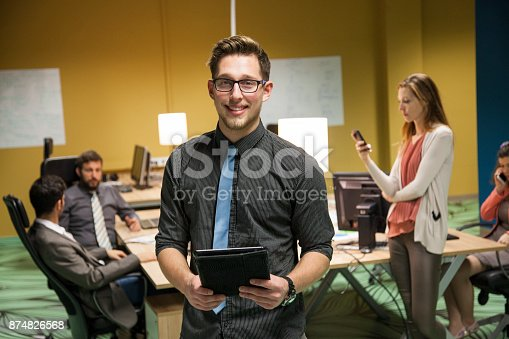 624700110istockphoto Young businessman in office with colleagues in background 874826568