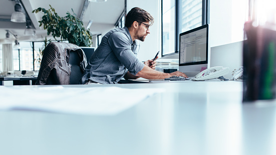 Young businessman in office working on computer