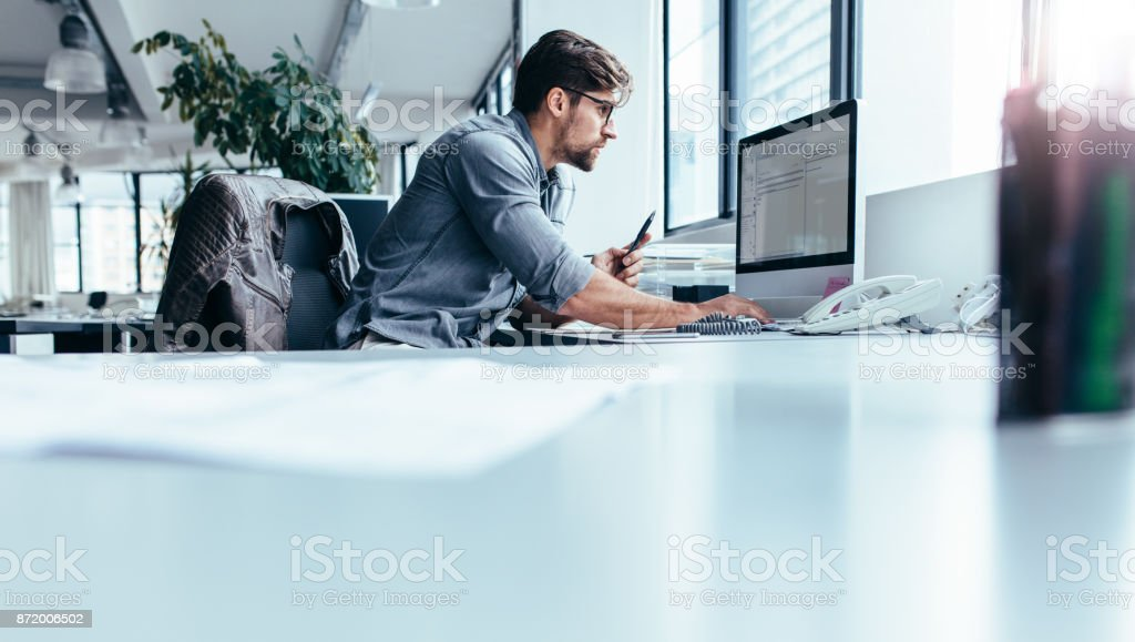 Young businessman in office working on computer stock photo