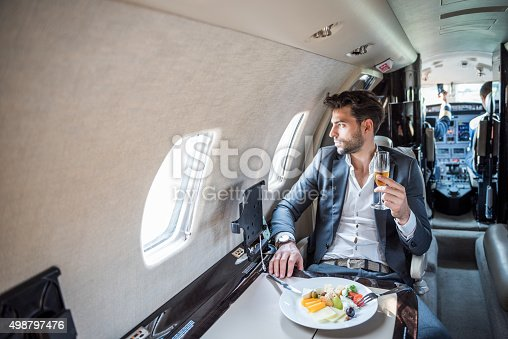 istock Young businessman in private jet airplane 498797476