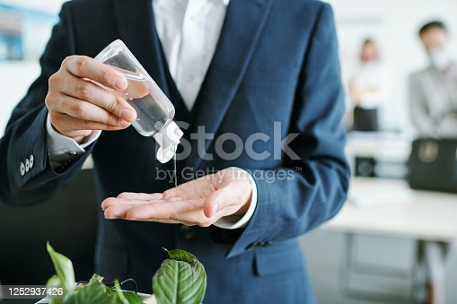 Young elegant businessman in suit dripping sanitizer from plastic bottle on his hands in the beginning of working day in office