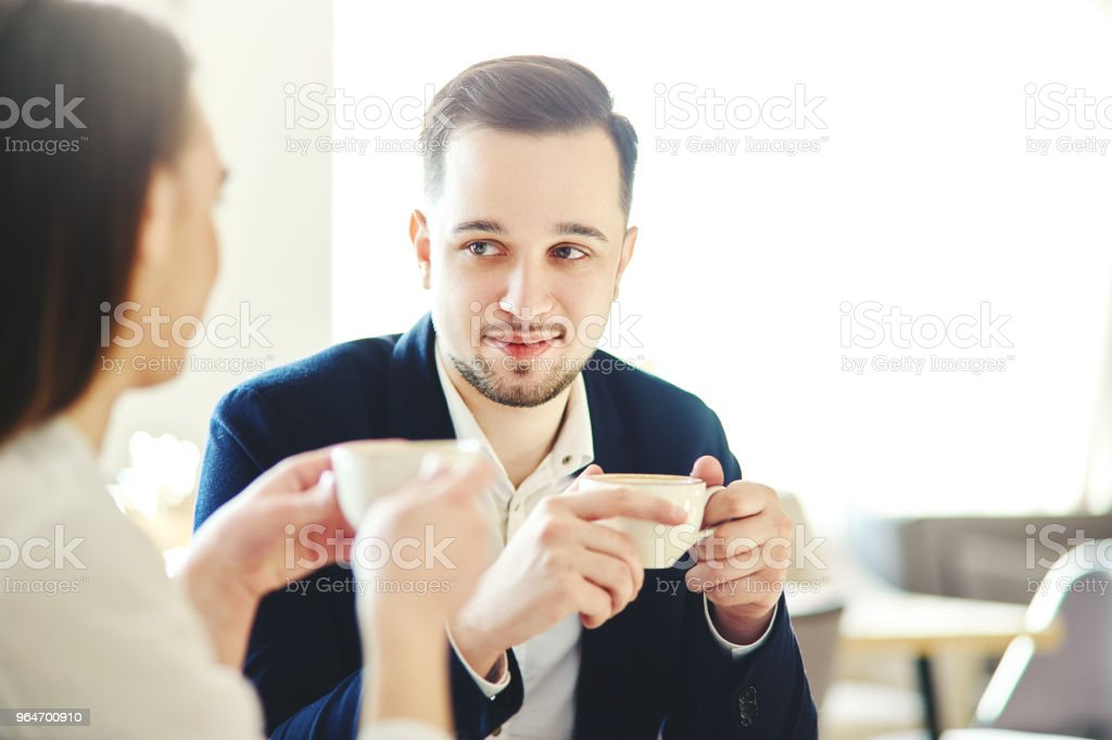 Young businessman in suit looking at his female colleague during business talk in cafe. Business partners having coffee together royalty-free stock photo