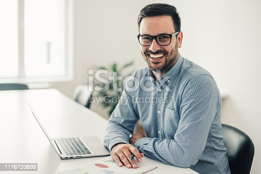 Shot of a young smiling businessman working on a laptop in the office.