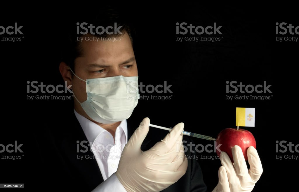 Young businessman injecting chemicals into an apple with Vatican City flag on black background stock photo
