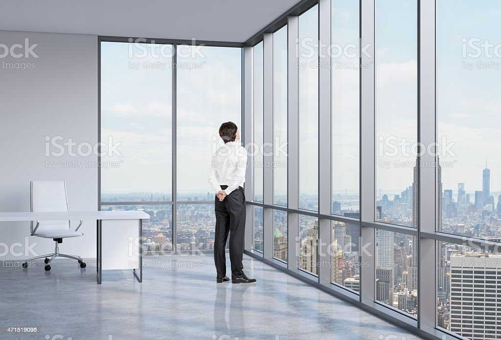 Young businessman is looking through the corner window. stock photo