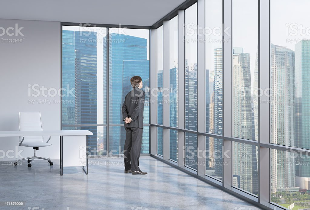 Young businessman is looking through the corner window. Singapore background. stock photo