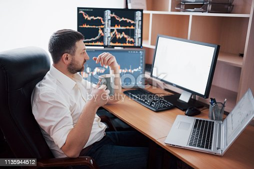 508901890 istock photo Young businessman is sitting in office at table, working on computer with many monitors,diagrams on monitor. Stock broker analyzes binary options charts.Hipster man drinking coffee,studying 1135944512
