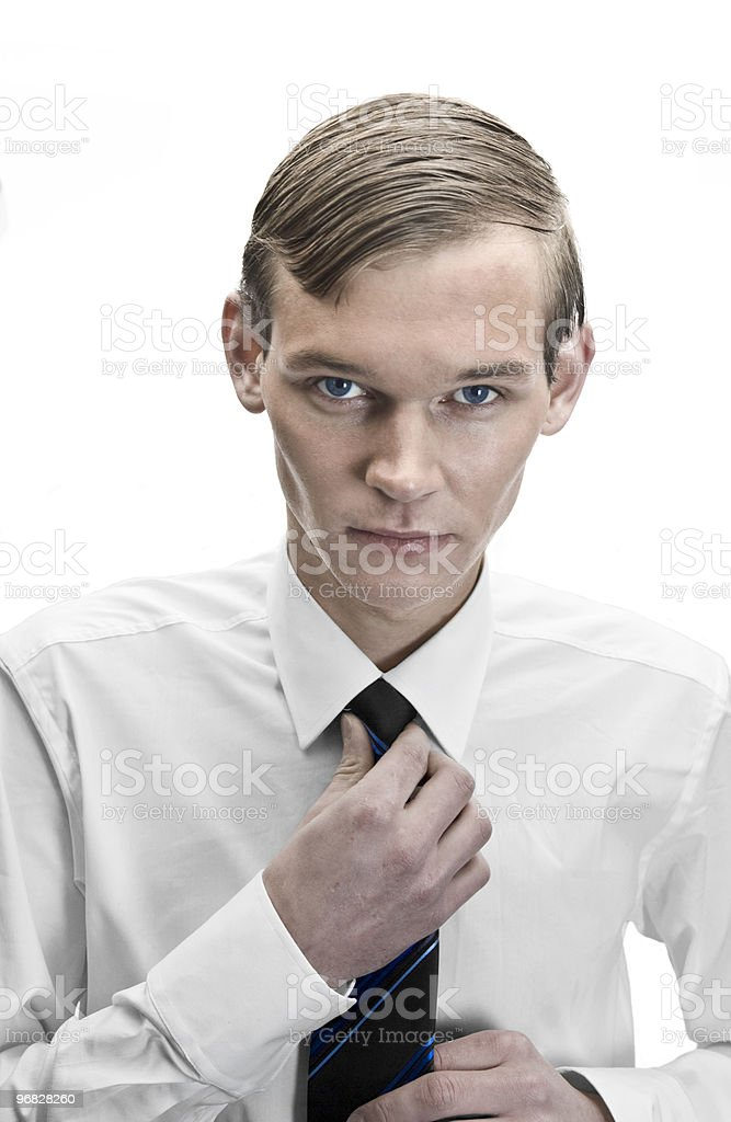 young businessman is tying his tie royalty-free stock photo