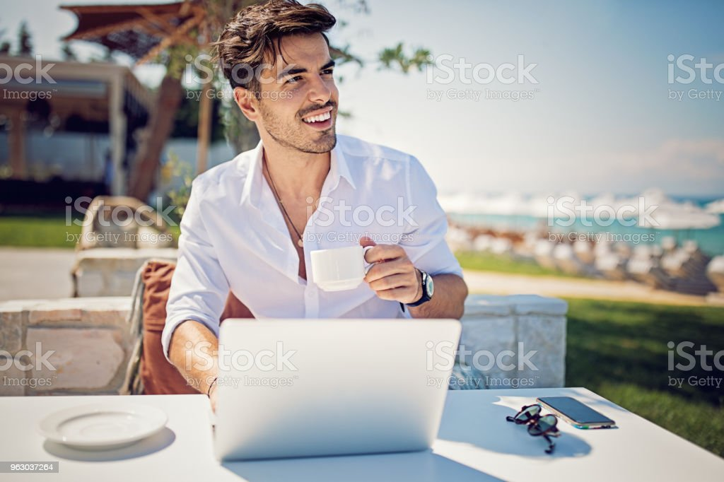 Young businessman is working and drinking coffee on the beach stock photo