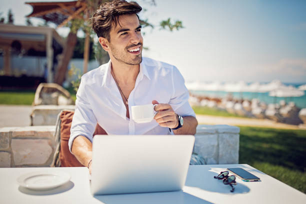 young businessman is working and drinking coffee on the beach - enjoying wealthy life imagens e fotografias de stock