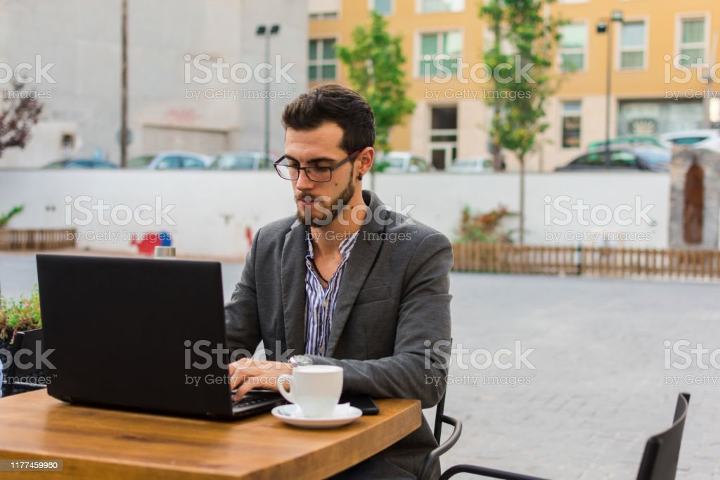 Young businessman is working in a bar terrace with his laptop and smartphone Young businessman is working in a bar terrace with his laptop and smartphone. Work, lifestyle Adult Stock Photo